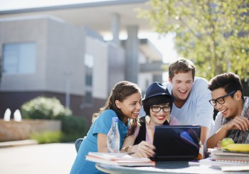 Students using laptop together outdoors